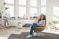 Relaxed woman at home sitting in chair - RBF004554