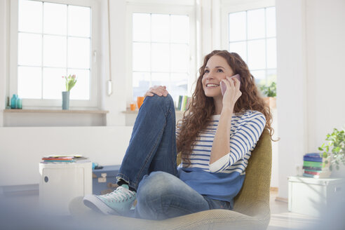 Woman at home sitting in chair talking on cell phone - RBF004557