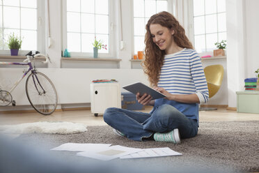Woman at home sitting on floor using digital tablet - RBF004563