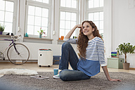 Smiling woman at home sitting on floor - RBF004566
