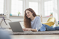 Woman at home lying on floor using laptop - RBF004569