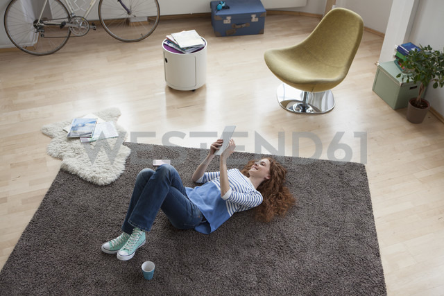 Woman at home lying on floor using digital tablet - RBF004572