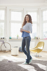 Smiling woman at home holding cup of coffee - RBF004575