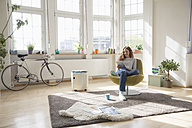 Woman at home sitting in chair using digital tablet - RBF004584