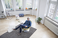 Relaxed mature man at home sitting in chair listening to music - RBF004587