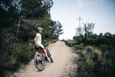 Mountain biker having a rest on a trail - JRFF000725