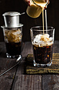 Pouring sweetened condensed milk over vietnamese iced coffee - SBDF002902