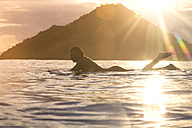 Indonesia, Sumbawa island, female surfer lying on surfboard in the evening - KNTF000288