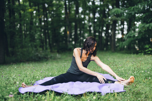 Young woman stretching out in nature, yoga in nature - LCU000006