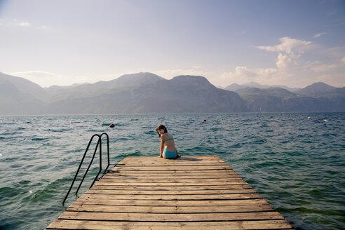 Italy, Brenzone, girl sitting on jetty - LVF004905