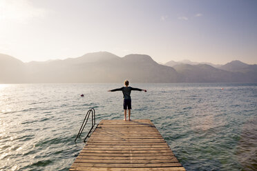 Italy, Brenzone, back view of boy standing on jetty - LVF004911