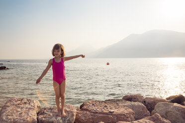 Italy, Brenzone, little girl drying wearing swimsuit standing at lakeshore - LVF004917