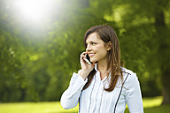 Smiling young woman telephoning with smartphone in a park - FMKF002712