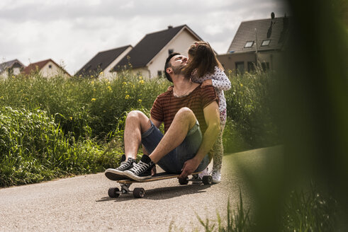 Daughter kissing father on skateboard - UUF007401