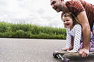 Daughter with father on skateboard - UUF007404