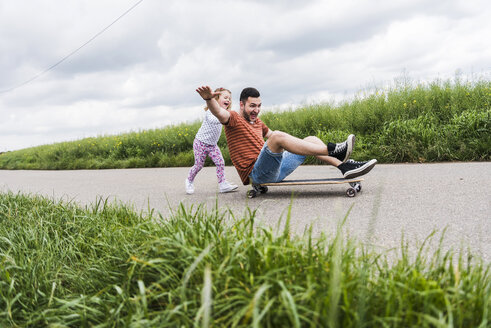 Daughter pushing father on skateboard - UUF007407