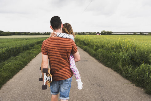 Father with skateboard carrying daughter on country lane - UUF007413