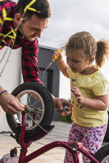 Father and daughter repairing bicycle together - UUF007419