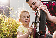 Father and daughter repairing bicycle together - UUF007422