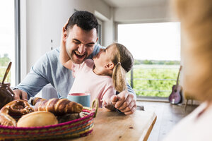 Playful daughter with father at breakfast table - UUF007434