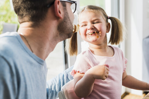 Playful father and daughter with food in mouth - UUF007440