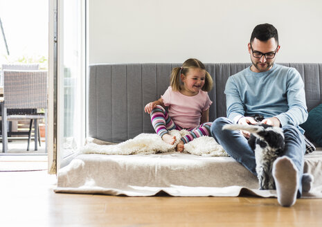 Father and daughter with dog at home - UUF007443