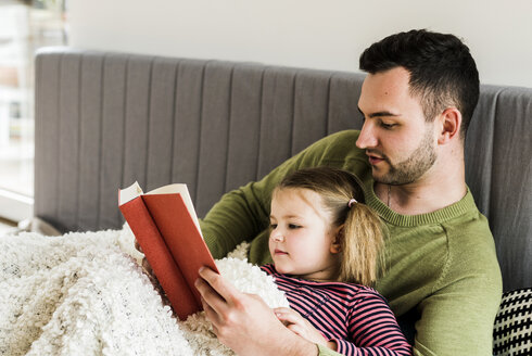 Father and daughter reading a book at home - UUF007455
