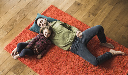 Father and daughter lying on carpet on the floor - UUF007464