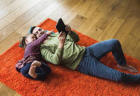 Father and daughter lying on carpet on the floor using digital tablet - UUF007467