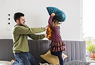 Father and daughter having a pillow fight - UUF007473