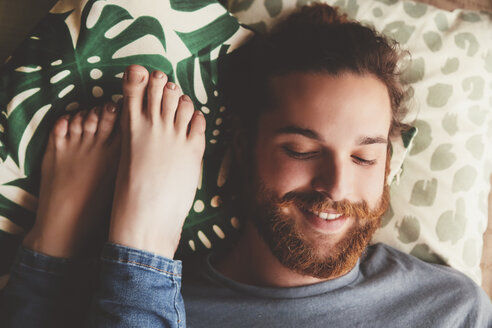 Portrait of smiling young man lying besides feet of his girlfriend - RTBF000224