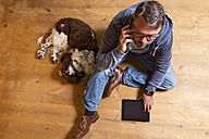 Overhead view of man on the phone on the floor next to dog - MAEF011755