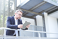Businessman using digital tablet outdoors - MAEF011758