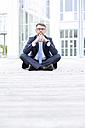 Businessman sitting outdoors thinking - MAEF011776