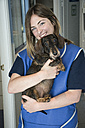Portrait of smiling veterinarian holding dog in her arms - ABZF000647