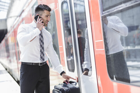 Businessman on cell phone getting into train - MADF000897