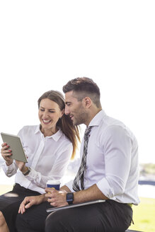 Businessman and businesswoman with digital tablet outdoors - MADF000903