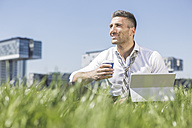 Germany, Cologne, smiling businessman with digital tablet in meadow - MADF000909