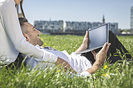 Business couple with digital tablet in meadow - MADF000912