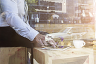 Businessman using digital tablet in a cafe - MADF000915