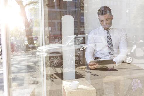 Businessman using digital tablet in a cafe - MADF000918
