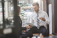 Businessman and businesswoman with digital tablet and smartphone in a cafe - MADF000921