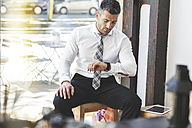 Businessman in a cafe checking the time - MADF000924
