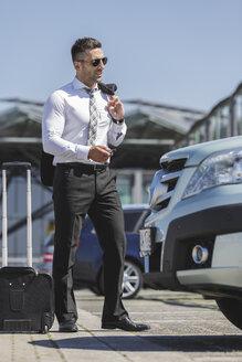 Businessman at car park opening car - MADF000942
