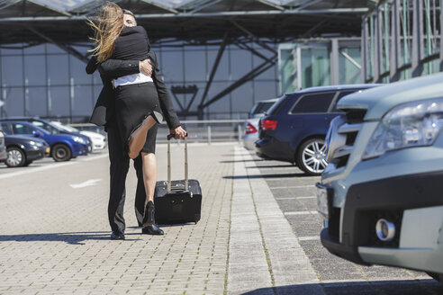 Businessman with luggage at car park hugging woman - MADF000948