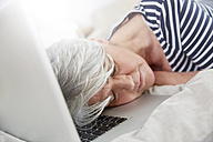 Exhausted woman sleeping on laptop - FMKF002725