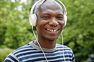Portrait of smiling man with headphones - FMKF002734