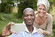 Portrait of couple taking selfie with smartphone - FMKF002737