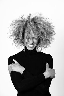Portrait of laughing woman with afro wearing black turtleneck pullover - JCF000004