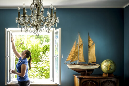 Home interior with vintage ship model and globe, woman cleaning windows - HAM000204